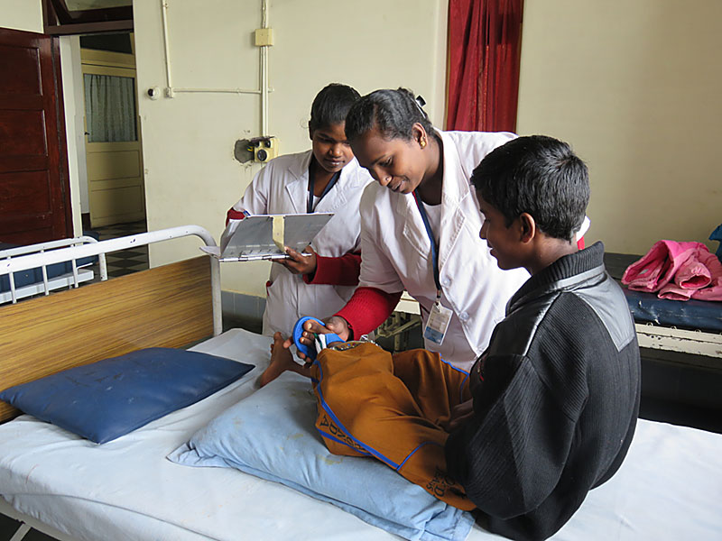 Crèche graduates, now nursing students, work with a patient at a local teaching hospital. A good start early in life gives crèche students an academic edge: almost all finish high school and many go on to trade school or college.